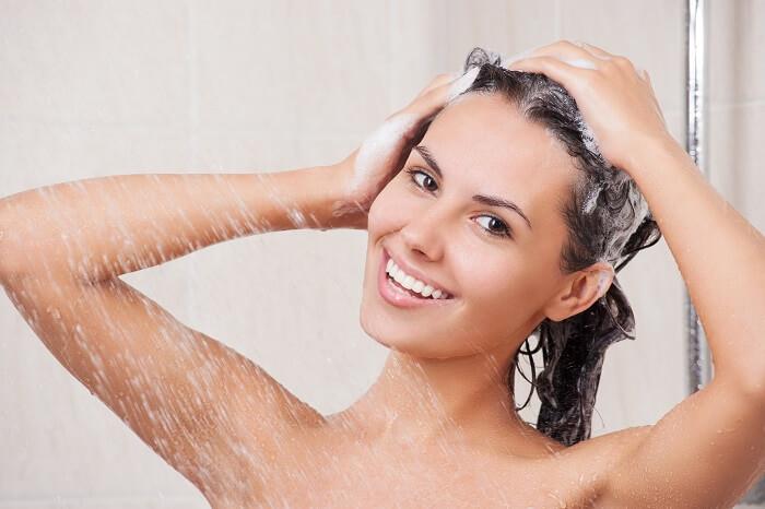 Frau wäscht Haare mit silikonfreien Shampoo